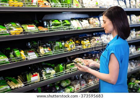 Portrait of a smiling woman doing shopping in supermarket - stock photo