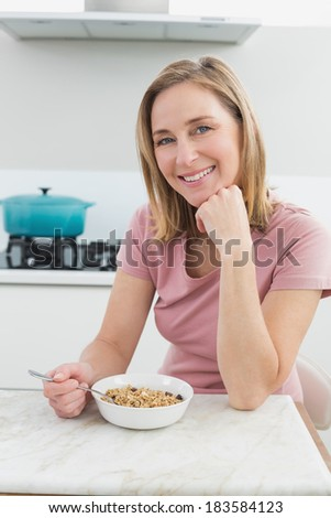 Portrait of a smiling woman having cereals in the kitchen at home - stock photo