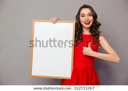 Portrait of a smiling woman holding blank board and showing thumb up over gray background - stock photo