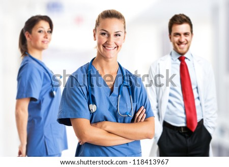 Portrait of a smiling woman in front of her medical team - stock photo