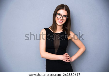 Portrait of a smiling woman in glasses over gray background. Wearing in trendy black dress. Looking at the camera - stock photo