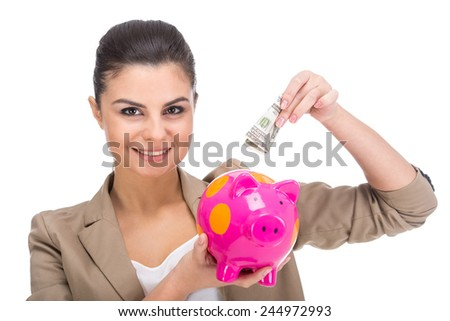 Portrait of a smiling woman is putting money on a piggy bank, isolated on a white background. - stock photo