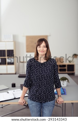 Portrait of a Smiling Woman Leaning her Back Against the Table Inside the Office While Looking at the Camera. - stock photo