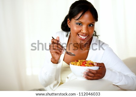 Portrait of a smiling woman looking at you and having breakfast while is sitting on sofa at home indoor. with copyspace - stock photo