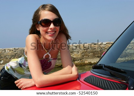 Portrait of a smiling woman on a car - stock photo