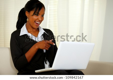 Portrait of a smiling woman on black suit pointing to laptop screen while sitting on sofa at home indoor - stock photo
