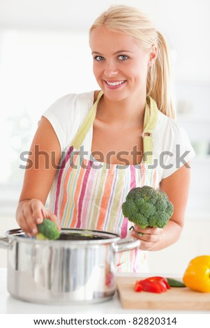 Portrait of a smiling woman putting cabbage on water while looking at the camera - stock photo