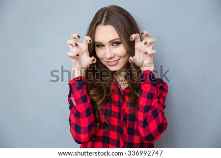 Portrait of a smiling woman reading for scratch with nails over gray background - stock photo