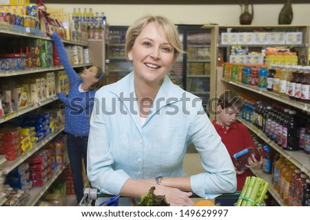 Portrait of a smiling woman shopping with son and daughter in supermarket - stock photo