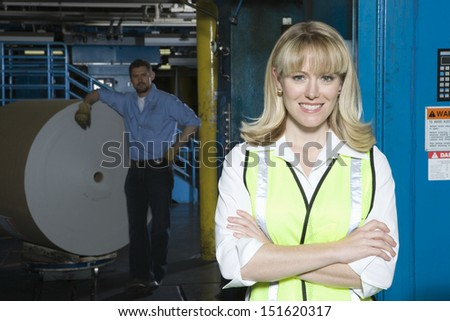 Portrait of a smiling woman with man by huge roll of paper in the background at newspaper factory - stock photo