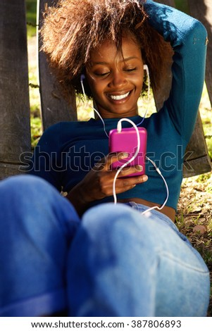 Portrait of a smiling young african american woman with mobile phone and earphones - stock photo