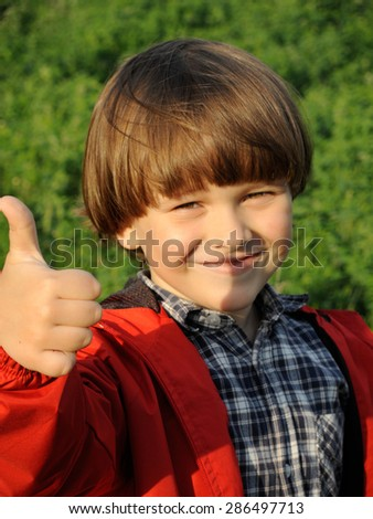 Portrait of a smiling young boy gesturing thumbs on the nature. Happiness, fashionable concept. Lifestyle. - stock photo