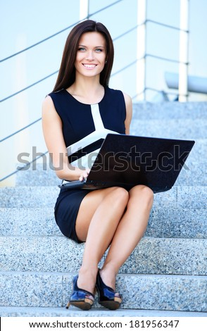 Portrait of a smiling young business woman using laptop on steps outdoors  - stock photo