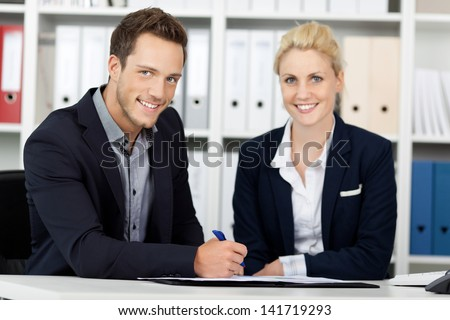 Portrait of a smiling young businessman and woman sitting at office desk - stock photo