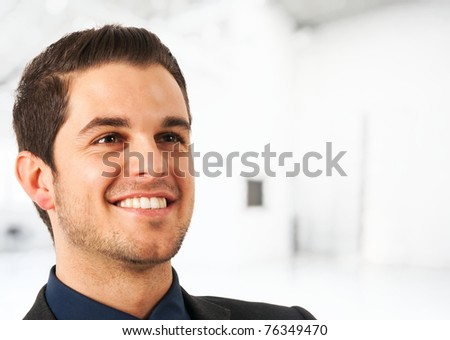 Portrait of a smiling young businessman. Blurred bright background. - stock photo