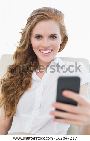 Portrait of a smiling young businesswoman with cellphone in a bright office - stock photo