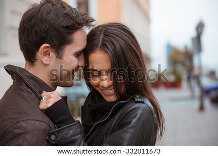 Portrait of a smiling young couple hugging outdoors - stock photo