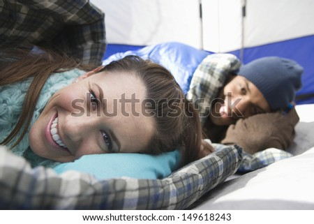 Portrait of a smiling young couple lying in sleeping bags in tent - stock photo