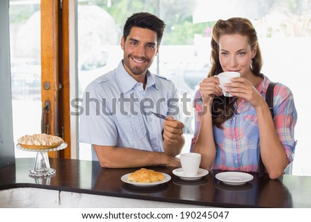 Portrait of a smiling young couple with man holding credit card at the coffee shop - stock photo