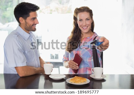 Portrait of a smiling young couple with woman holding out credit card at the coffee shop - stock photo