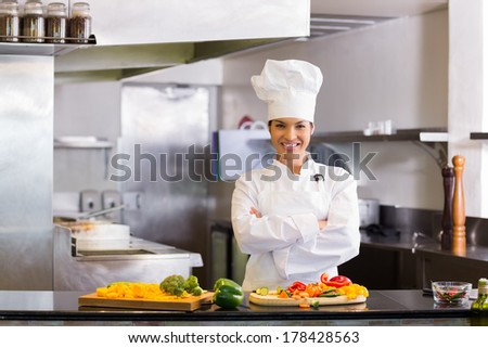 Portrait of a smiling young female chef standing with cut vegetables in the kitchen - stock photo