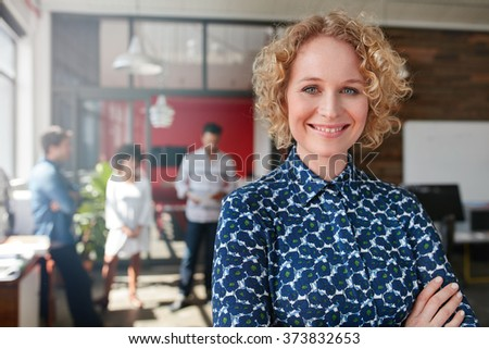 Portrait of a smiling young female designer standing in her office with some colleagues in the background. - stock photo