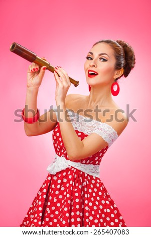 Portrait of a smiling young female model with hand-held telescope in her arms wearing red dress - stock photo