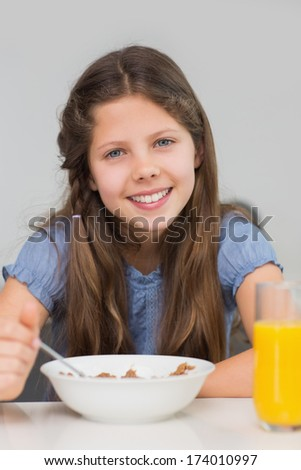 Portrait of a smiling young girl enjoying breakfast in the kitchen at home - stock photo
