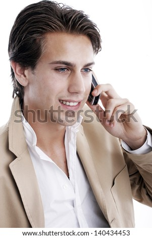 Portrait of a smiling young handsome playboy talking on the mobile phone on a white background - stock photo
