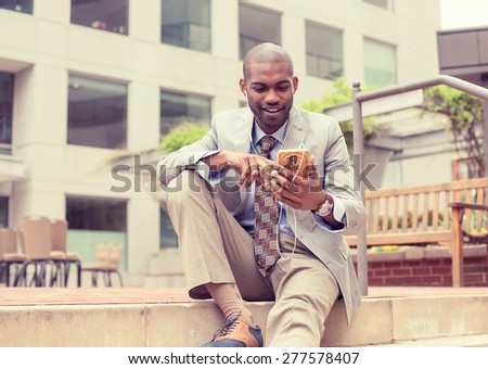 Portrait of a smiling young happy man listening to music on cellphone sitting outdoors on sunny day. Positive face expression  - stock photo