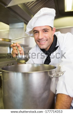 Portrait of a smiling young male cook tasting food in the kitchen - stock photo