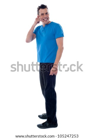 Portrait of a smiling young man giving call gesture on white background - stock photo