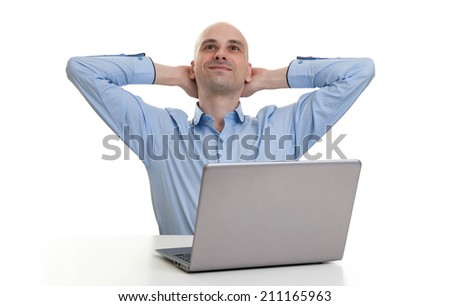 Portrait of a smiling young man relaxing and sitting at desk with laptop computer - stock photo