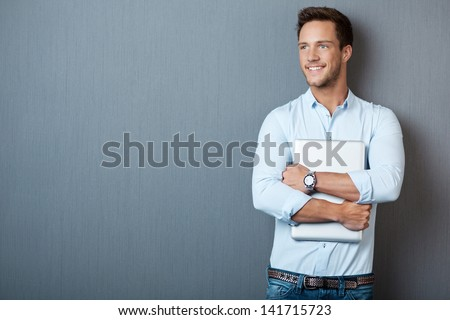 Portrait of a smiling young man standing with laptop against blue background - stock photo