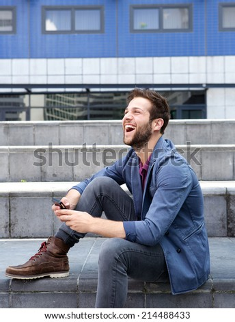 Portrait of a smiling young man text messaging on cellphone - stock photo