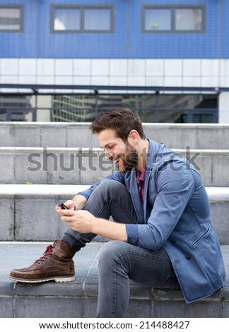 Portrait of a smiling young man text messaging on mobile phone - stock photo