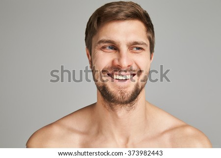 Portrait of a smiling young man with bare swimmers shoulders on a gray background, powerful, beard, charismatic, adult, brutal, athletic, edited photo, bright smile, white teeth smile, look toward - stock photo