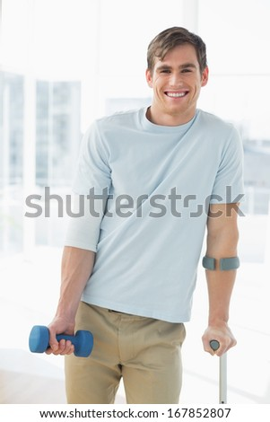 Portrait of a smiling young man with crutch and dumbbell at the gym hospital - stock photo
