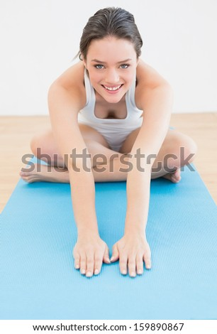 Portrait of a smiling young sporty woman sitting and stretching hands on exercise mat - stock photo