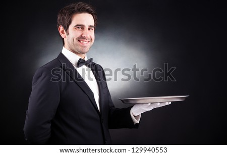 Portrait of a smiling young waiter holding an empty dish on black background - stock photo