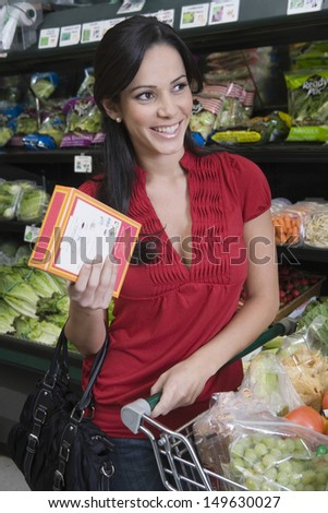 Portrait of a smiling young woman food shopping in supermarket - stock photo