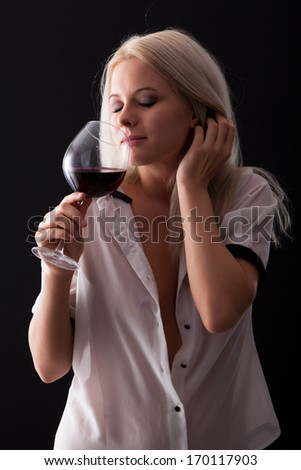 Portrait of a smiling young woman holding a glass of red wine  - stock photo