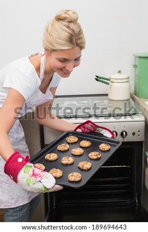 Portrait of a smiling young woman removing a tray of cookies from the oven in kitchen - stock photo