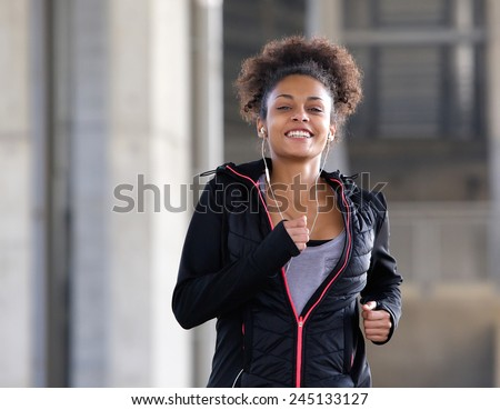 Portrait of a smiling young woman running outdoors with earphones - stock photo