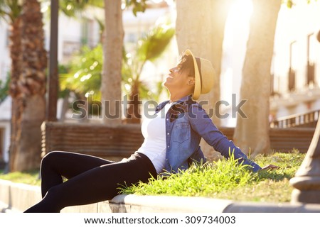 Portrait of a smiling young woman sitting outside enjoying life - stock photo