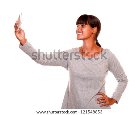 Portrait of a smiling young woman taking a photo with cellphone against white background - stock photo