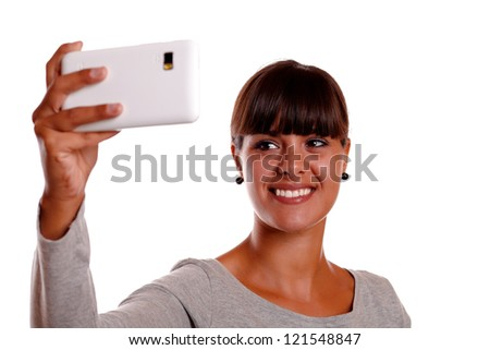 Portrait of a smiling young woman taking a picture with her cellphone against white background - stock photo