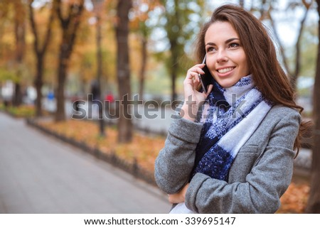 Portrait of a smiling young woman talking on the phone outdoors - stock photo
