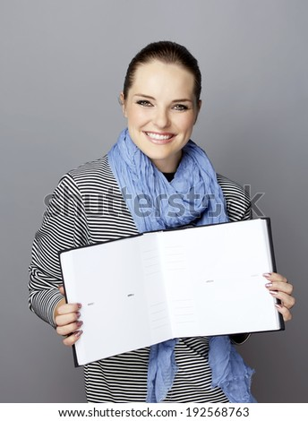 Portrait of a smiling young woman, with long brunette hair, on gray studio background, holding an open photobook or album in her hands  - stock photo