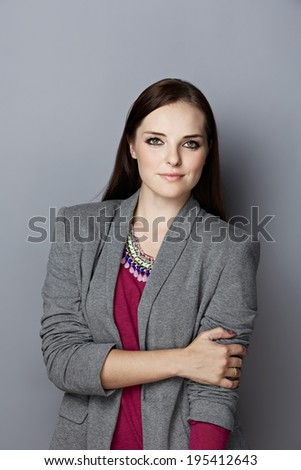 Portrait of a smiling young woman, with long brunette hair, on gray studio background, wearing pink purple top, gray blazer and bright statement necklace - stock photo
